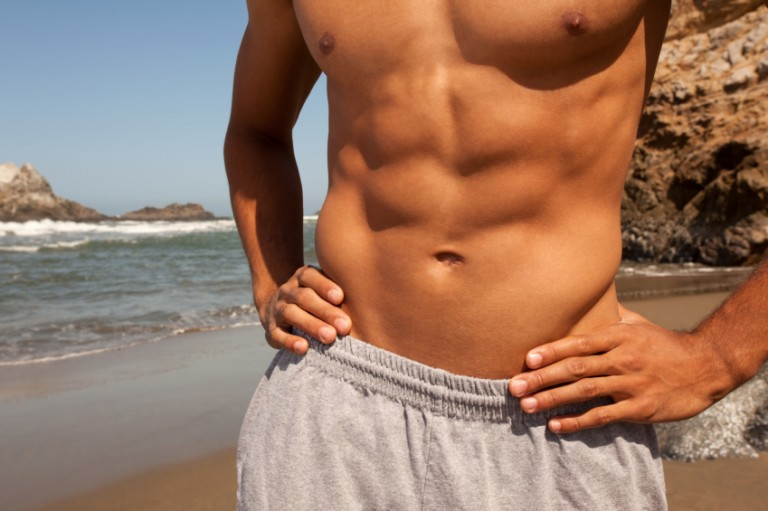 A fit young man shows off his abs on the beach under a clear blue sky.